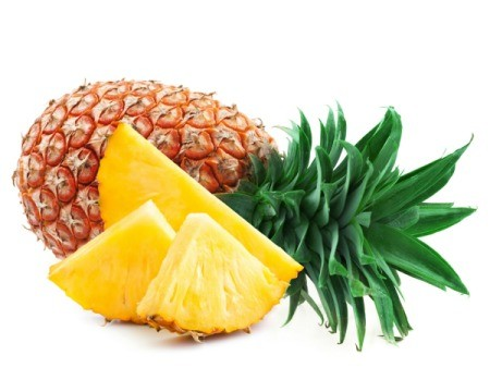 Whole fresh pineapple laying on it's size with fresh pineapple slices