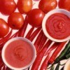 White bowls of tomato paste, tomato sauce, and salsa setting on a background of tomatoes and red and green peppers