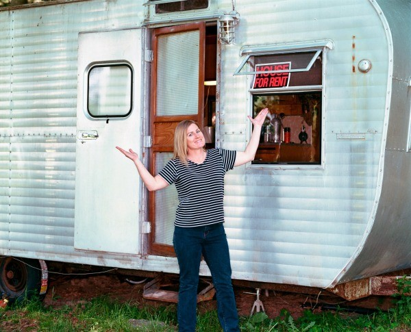 "Woman standing in front of a travel trailer that has a ""Home for Rent"" sign in the window"
