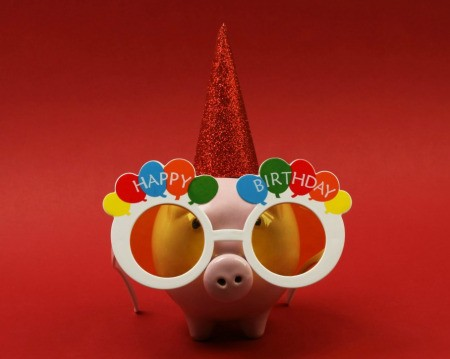 Piggy Bank wearing Happy Birthday glasses and a party hat against a red background