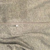 Close up of a small hole in a grey t-shirt