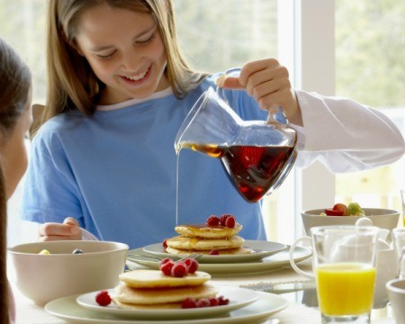 Girl pouring syrup on pancakes from a clear pitcher