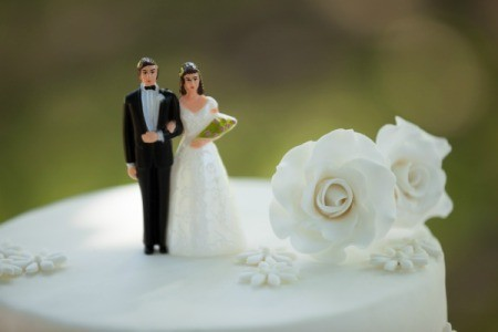 Bride and Groom figurines on the top of a wedding cake with a flower