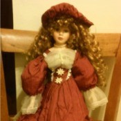 doll with red hair wearing a fancy rust colored dress with ecru lace