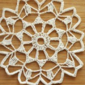 Starched white doily against a wooden background