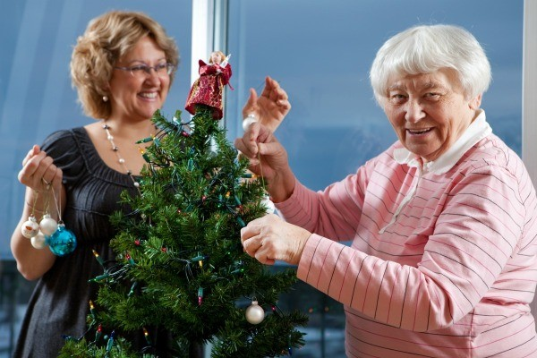 Volunteer helping senior adult woman decorate a Christmas Tree