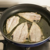 Fish fillets being fried in hot oil in a frying pan on stove