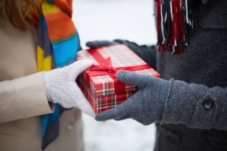Hands of two people in winter coats and gloves exchanging a gift.
