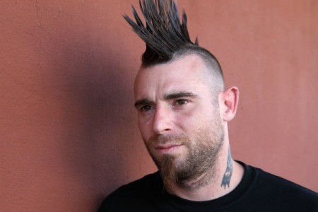 Man with spiked mohawk against brick colored background
