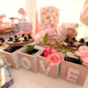 "Boxes spelling ""LOVE"" displayed on a dessert buffet"