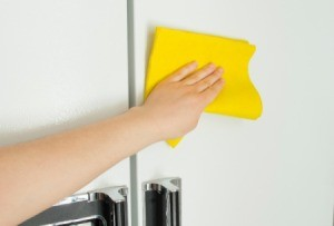 Hand cleaning the front of a refrigerator with a yellow cloth