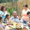 Several generations of a family laughing around a decorated table outdoors.