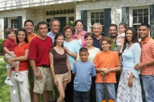 Several generations of a large family posed for a photo in front of home.