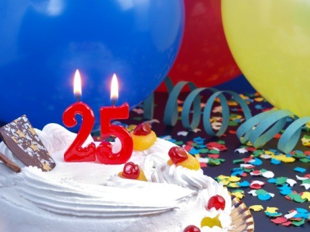 Candles in the shape of the number 25 on a cake in front of balloons, confetti and streamers