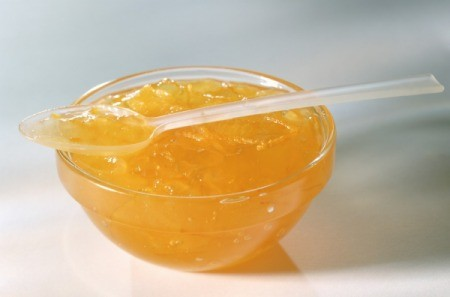 Orange Jelly (or marmalade) in a glass bowl with a clear plastic spoon of jelly laying across the top