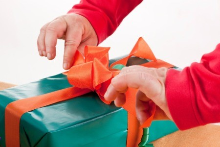 Hands opening a wrapped green gift with a red bow.