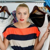 Woman framed by hanging clothing looking concerned