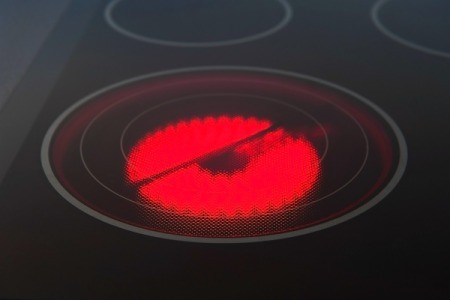 Red lit burner on a glass top stove