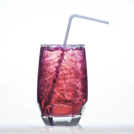 Glass of Grape soda with ice and a straw against a white background