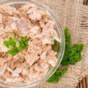 Clear glass bowl of dry looking tuna salad, garnished with parsley.