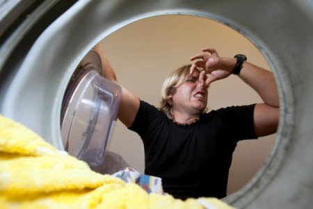 View from inside of a front load washing machine of a man holding his nose.
