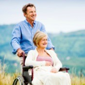 Man pushing woman in a wheelchair against a beautiful view.
