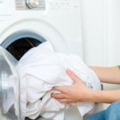 Woman removing white laundry from the dryer