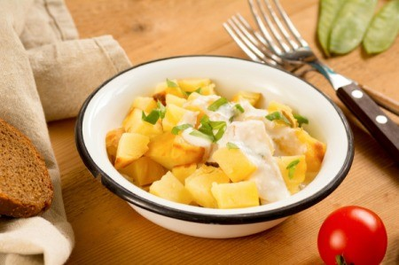 Bowl of potato salad using yellow potatoes and a dressing over the top