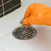 Orange gloved hands removing hair from a bath tub drain
