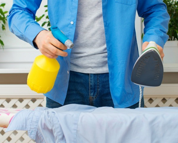 Man holding spray bottle in one hand and an iron in the other