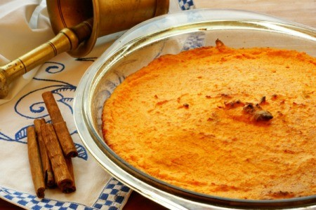 Carrot Souffle in glass dish with sticks of cinnamon beside it.