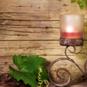 Candle on wrought iron scroll design holder with imitation grape vines