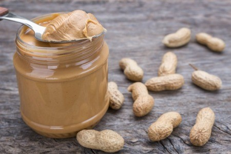 Jar of peanut butter with spoonful of peanut butter resting on top.  Peanuts are spread around the jar.