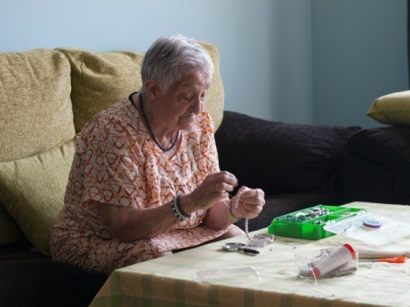 Elderly woman stringing beads