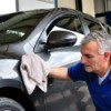 Man wiping car exterior with a cloth