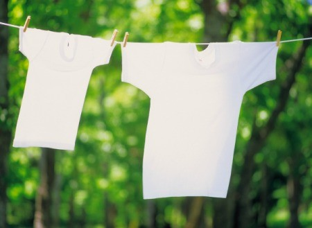 Two white t-shirts hanging on a clothes line