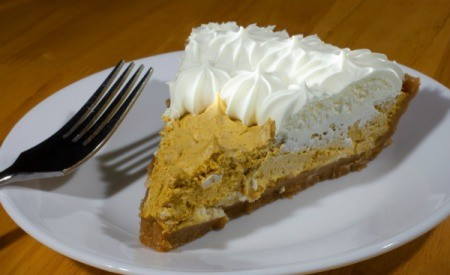 Slice of pumpkin mousse pie with whip cream and a fork on a white plate