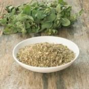 Fresh oregano and bowl of dried oregano on wooden surface