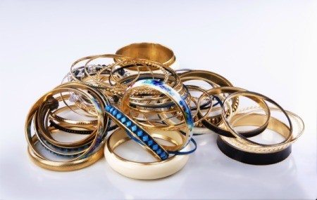 Unorganized pile of gold bracelets on a white surface