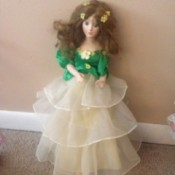 doll wearing dress with green top and three layered skirt