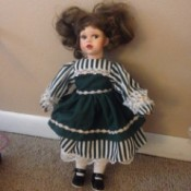 doll wearing a striped dress with green overskirt