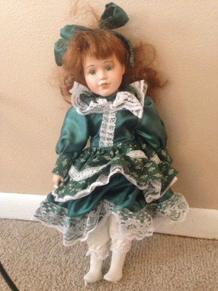 doll wearing a green dress and hat