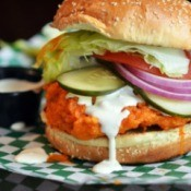 Close up of a chicken sandwich with dressing pouring out from between the buns