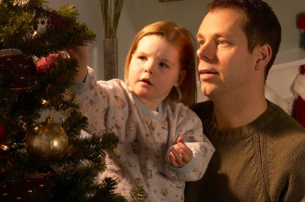 Father and young girl decorating a Christmas tree