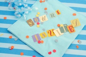 """You're Invited"" Spelled out on a napkin"