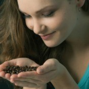 Woman with long hair smelling coffee beans in her cupped hands