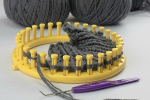 Yellow Knifty Knitter Loom with partial weaving made with grey yarn