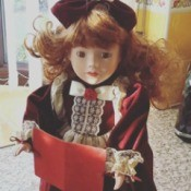 red haired doll in maroon dress holding a book