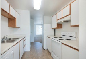 Old fashioned kitchen with white laminate cabinets and white Formica Counters