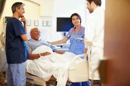Smiling man in hospital bed surrounded by 3 doctors